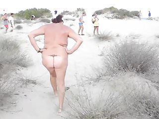 Nudist old woman on public beach