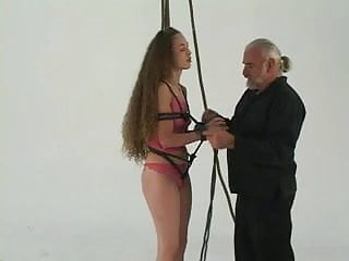 Ponytailed master ropes young bondage brunette to lift her with pulleys