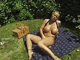 Oiling her tits and masturbating in a park